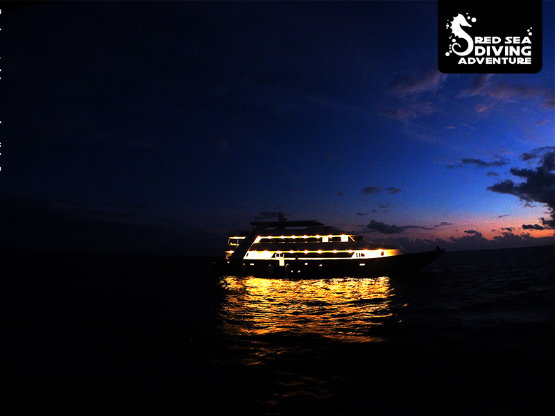 With the exterior lights on and a sun that is setting behind the horizon a yacht at sea looks stunning.